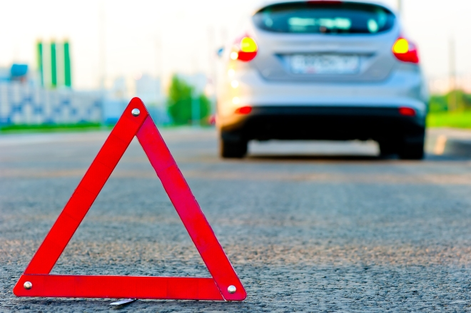 warning triangle on the road and the car moved down to the curb